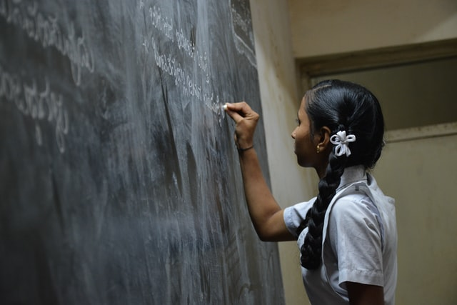 Young girl writing on a chalkboard at an educational nonprofit