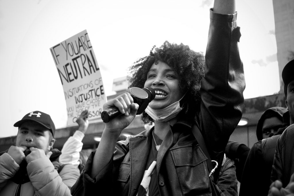 Image of a black woman smiling at a social justice event with the ACLU, an example of 501c4 organization.