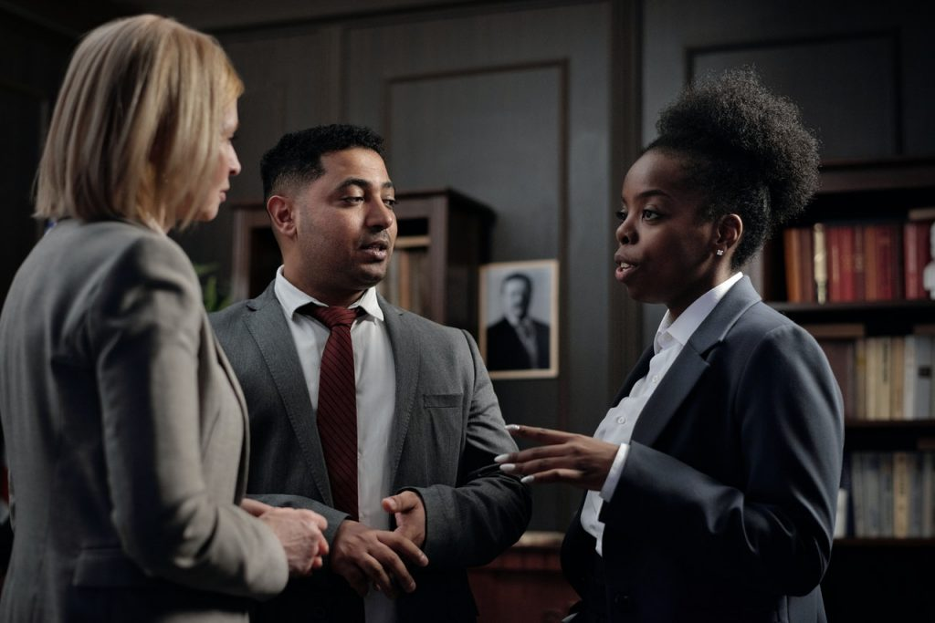 Three people in business suits having a conversation.