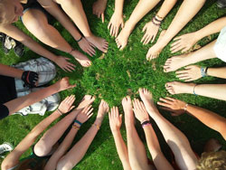 A group of people put their hands and feet together in the grass to make a circle of teamwork
