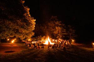 Children at summer camp sitting around a large bonfire