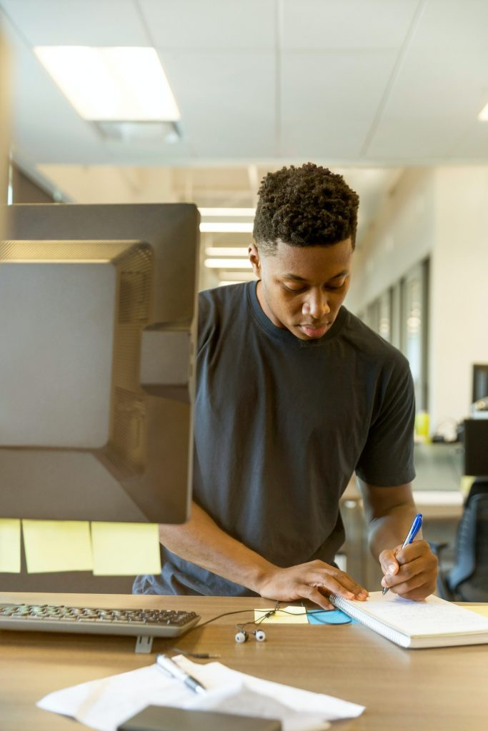 A man writes on a notebook while standing in front of a computer.