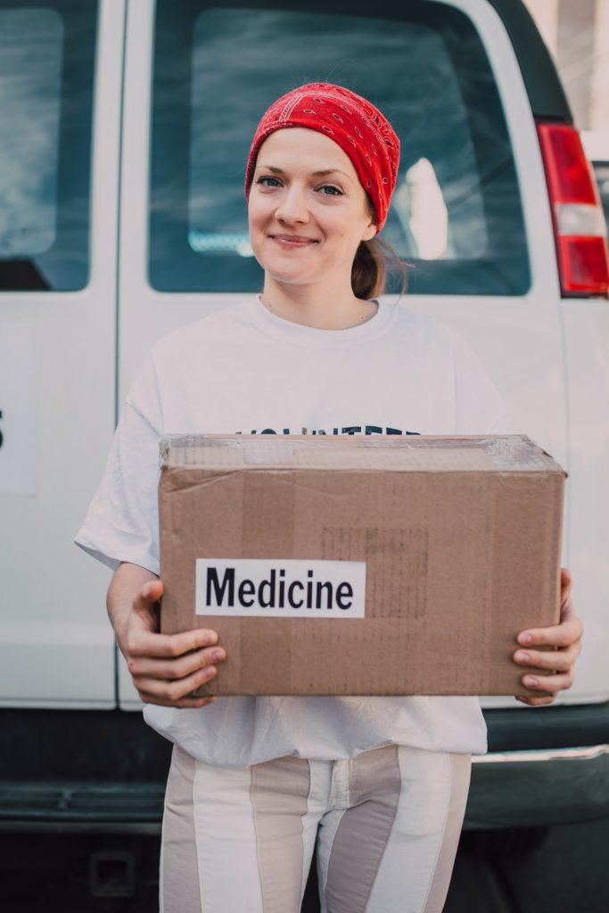 Female medical volunteer carries box of medicine.