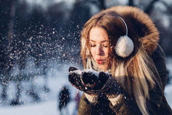 A woman in earmuffs blows into a scoop of fresh snow on her mittens