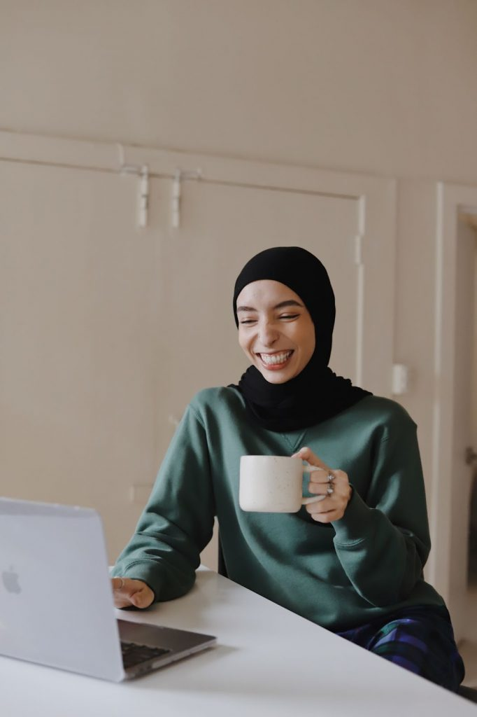 Remote nonprofit employee smiling and holding a cup of coffee at desk
