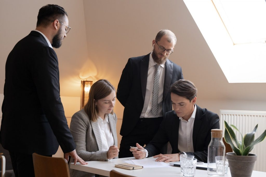 People in a formal setting discussing a form