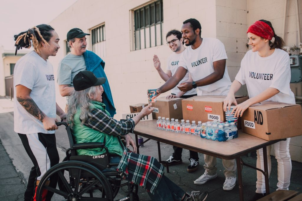 Volunteer giving food to a differently-abled elderly man in wheelchair