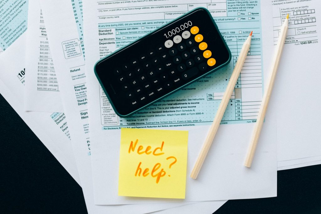 """501c3 compliance tax forms and a post-it note that says """"Need Help?"""""""