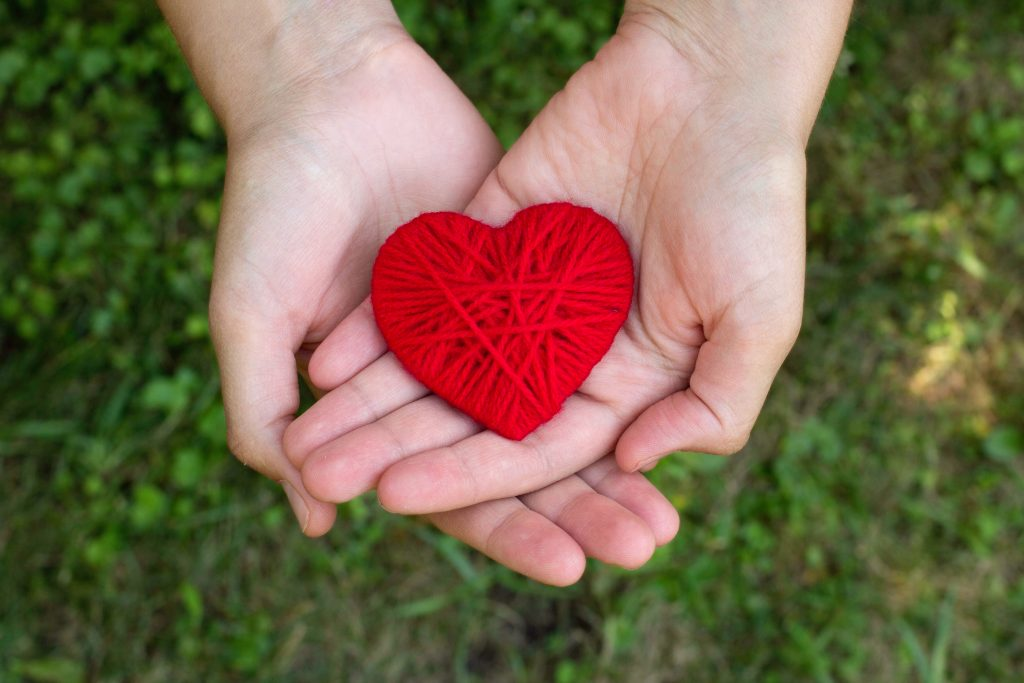 red woolen heart in a human hand, valentines day, love