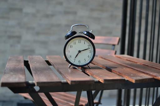 black alarm clock on wooden table