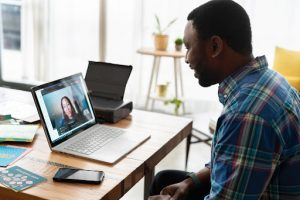 A man on a video conferencing call at work with a colleague at a nonprofit