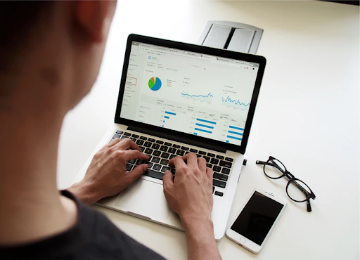 man looking at graphs on laptop