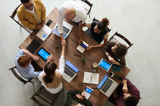 A photo of a nonprofit meeting around a table