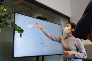Photo of a woman gesturing to recent project tasks at a nonprofit on a screen
